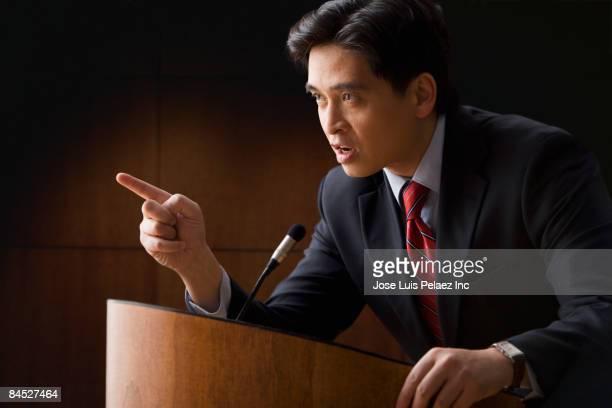 angry chinese businessman speaking at podium - político - fotografias e filmes do acervo