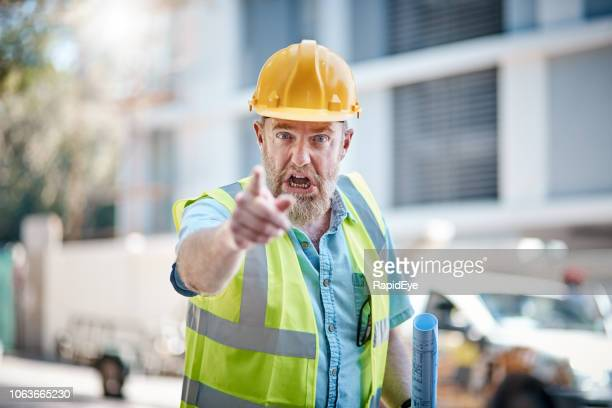 angry construction worker points and shouts in frustration - foreman stock pictures, royalty-free photos & images