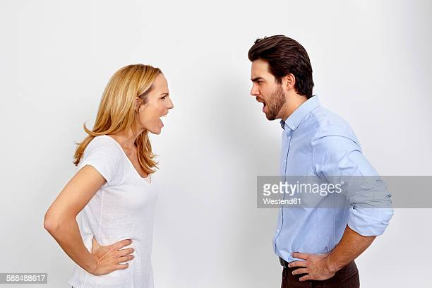 Angry couple shouting at each other in front of white background