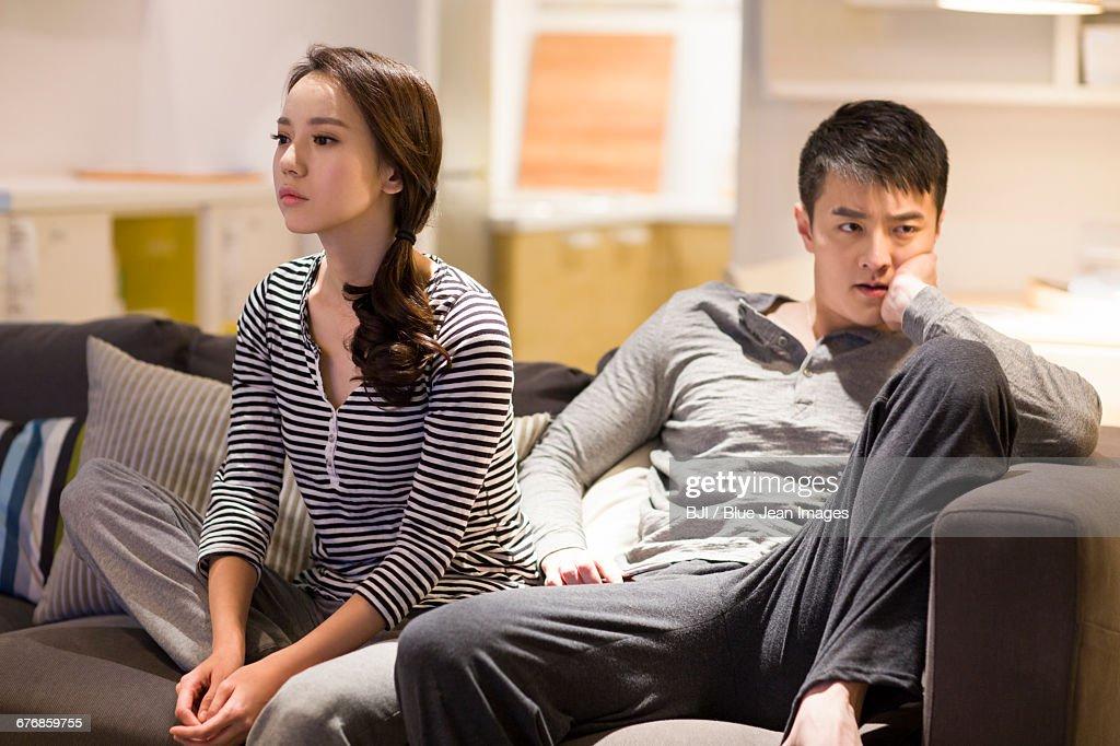 Angry couple sitting on living room sofa : Stock Photo