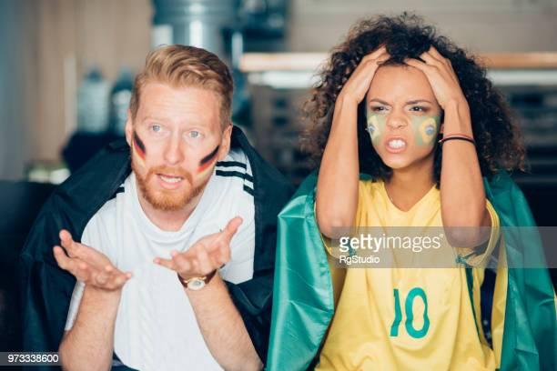 wütend paar unterstützt verschiedene nationale teams beobachten fußballspiel gemeinsam zu hause - trikot stock-fotos und bilder