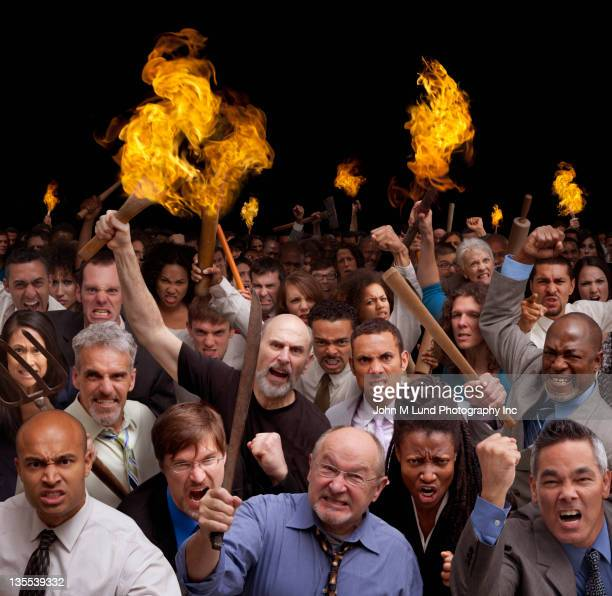 angry crowd carrying torches - mob stock photos and pictures