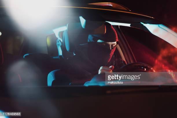arg rattfyllerist som sitter i bilen på bakgrunden av polis bil belysning - förföljande bildbanksfoton och bilder