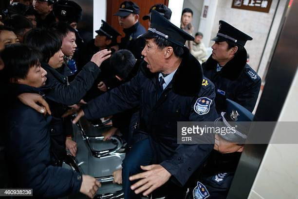 Angry family members clash with security personnel in a