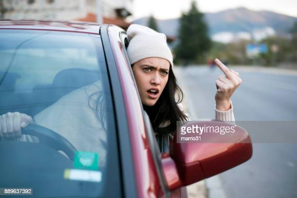 angry female driver showing the finger - car insurance stock pictures, royalty-free photos & images