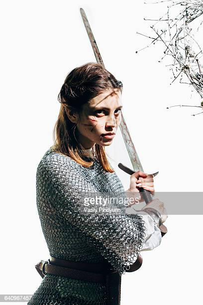 Angry female warrior wearing chain mail holding sword against white background
