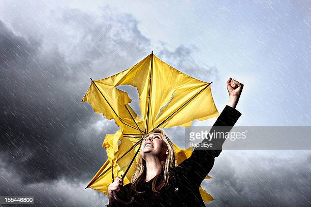Angry, frustrated woman with broken umbrella shaking fist at thunderstorm