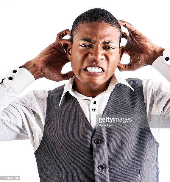 Angry, frustrated young man clutches his head