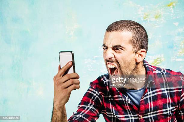Angry guy shouting to someone in his smartphone