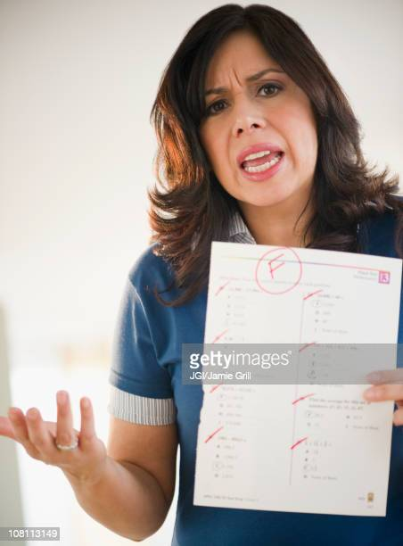 Angry Hispanic woman holding test paper with a failing grade