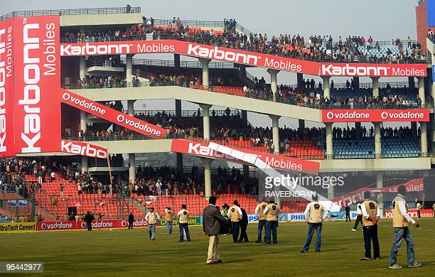Angry Indian cricket fans throw an advertising board after the cancellation of the fifth and final One Day International cricket match at The Feroz...