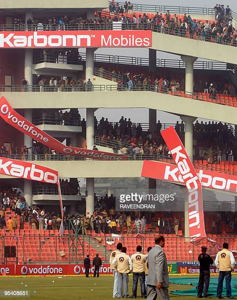 Angry Indian cricket fans throw billboards and chairs after the cancellation of the fifth and final One Day International cricket match at The Feroz...
