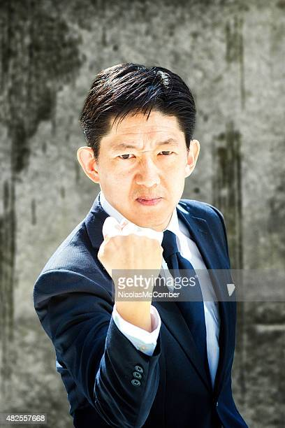 Angry Japanese businessman showing his fist with frown