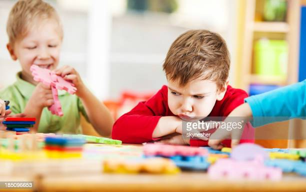 Angry little boy looking at puzzles.