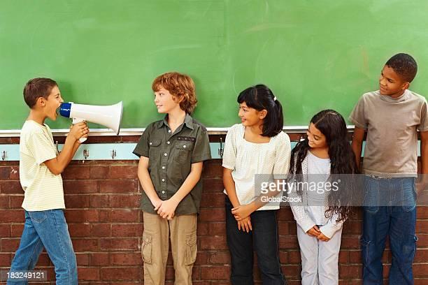 Colère petit garçon yelling à ses camarades de classe dans un porte-voix