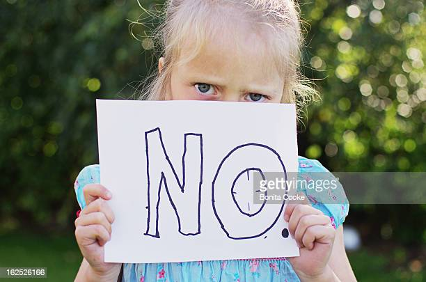 Angry little girl holding 'NO' sign