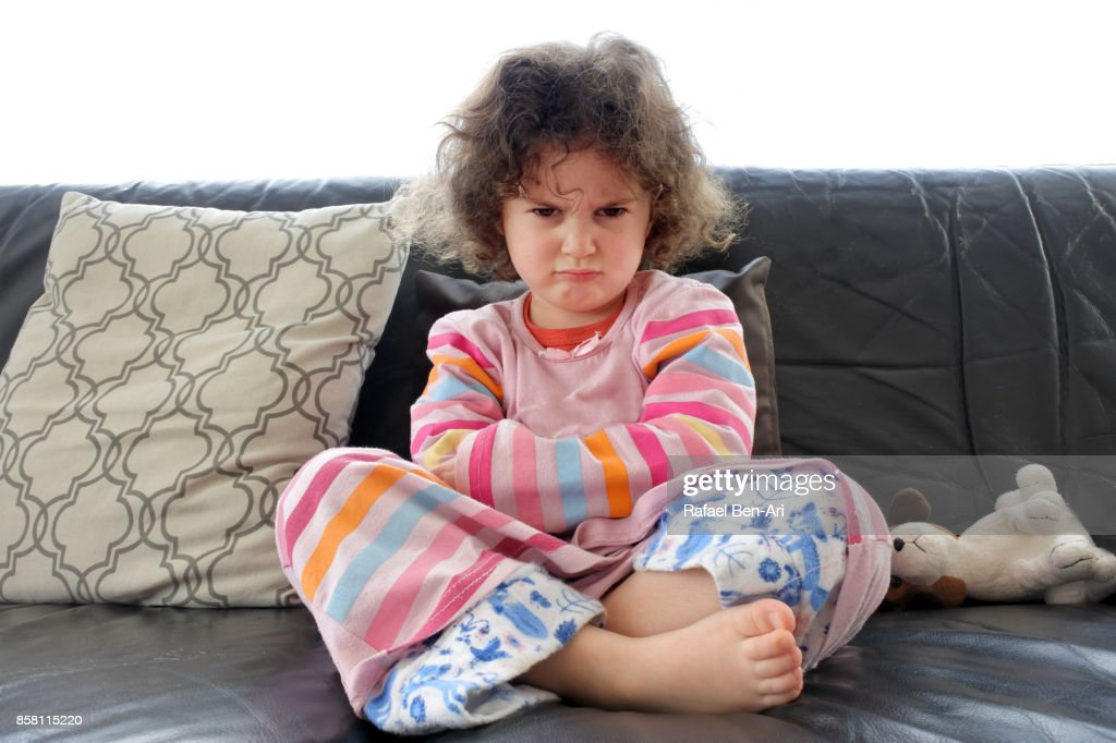 Angry little girl sits on a sofa : Stock Photo
