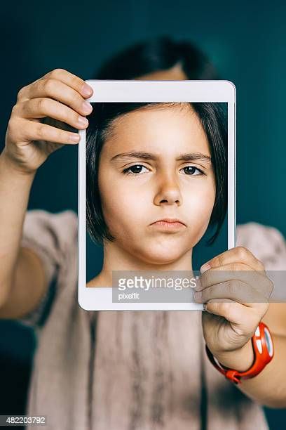 Angry little girl with digital tablet making selfie