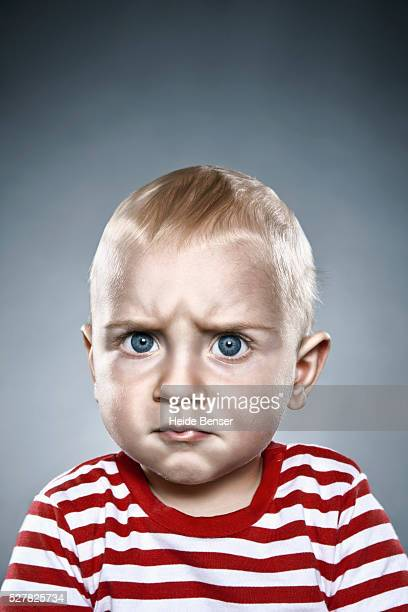 Angry looking baby boy in striped shirt