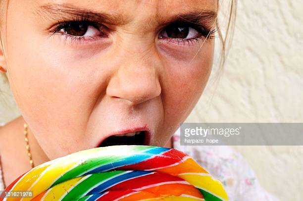 Angry looking girl with lollipop