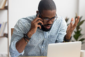 Angry mad african-american businessman talking on cellphone in office