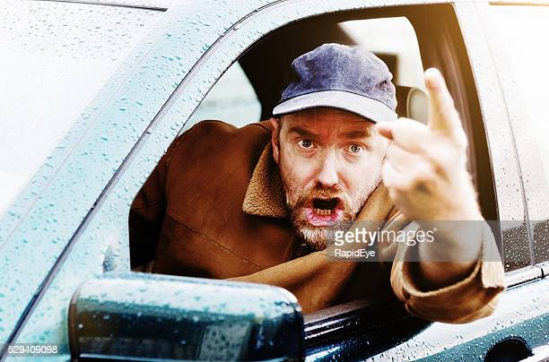 Angry male driver points finger accusingly, shouting  and threatening