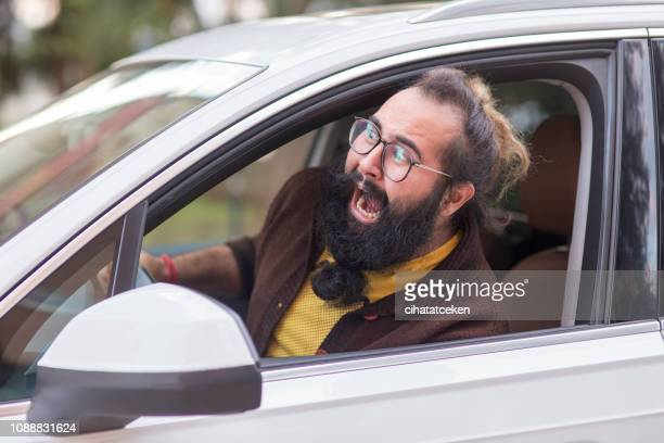 angry man behind the wheel demonstrating road rage - fury stock pictures, royalty-free photos & images