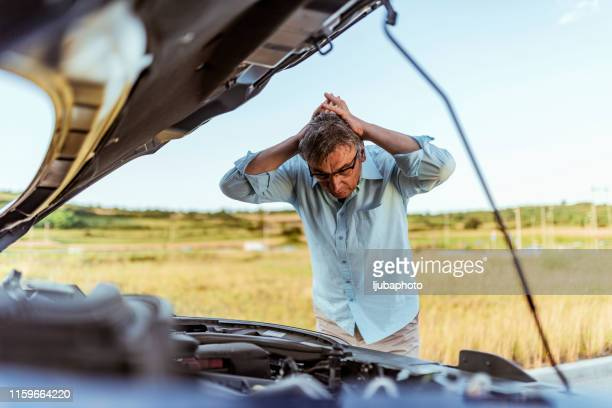 angry man checking his car - broken down car stock pictures, royalty-free photos & images