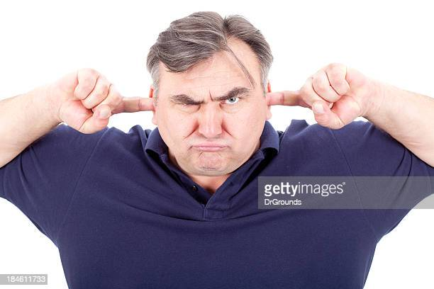 angry man covering his ears - fingers in ears stock pictures, royalty-free photos & images