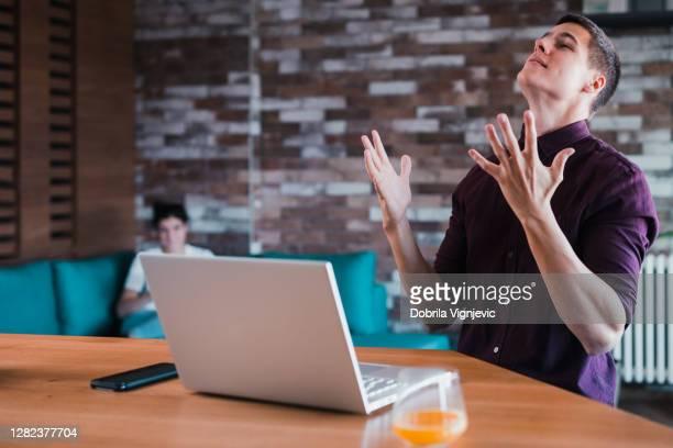 uomo arrabbiato che disapprova le cose che accadono quando lavora da casa - crisi foto e immagini stock