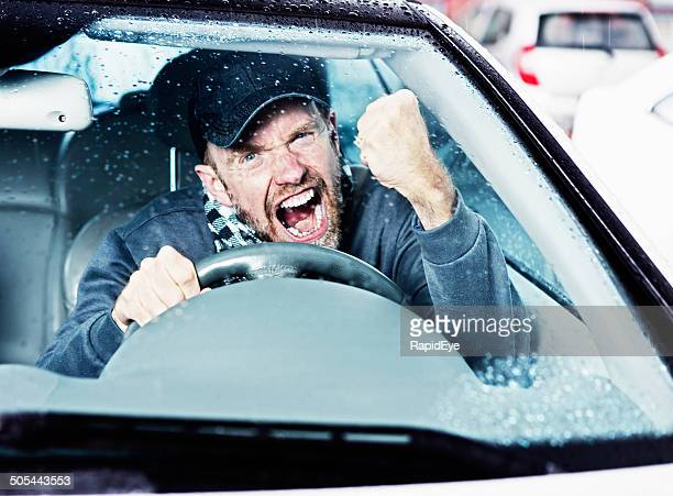 Angry man driving on rainy day shakes fist through windshield
