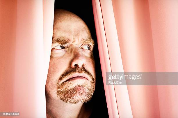 Angry man frowns, peering through closed curtains: noisy neighbours?