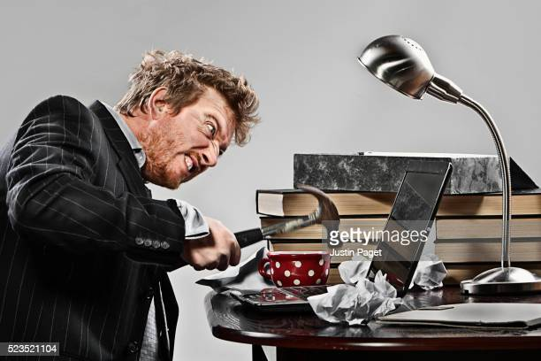 Angry man hammering laptop