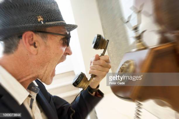 angry man in hat and glasses on old fashioned telephone - complaining stock pictures, royalty-free photos & images