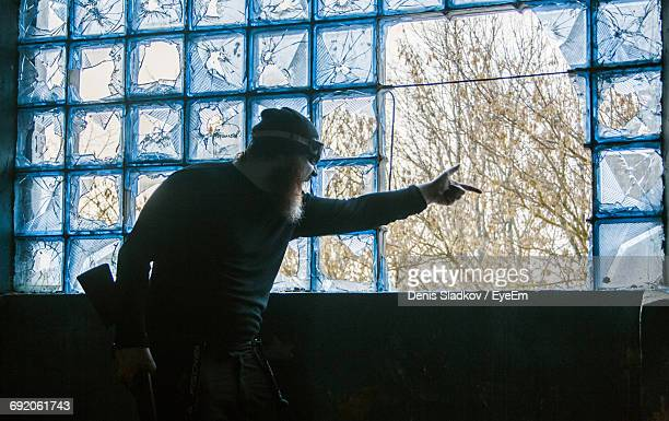 Angry Man Pointing Finger Towards Window In Abandoned Room