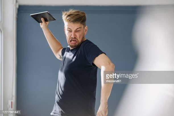angry man throwing tablet away - woede stockfoto's en -beelden