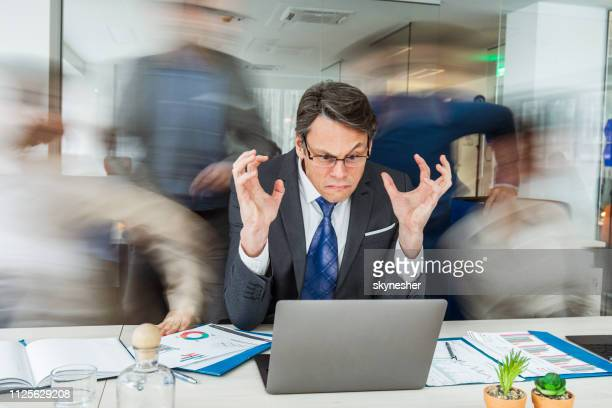 angry manager using laptop among his colleagues in blurred motion. - insanity stock pictures, royalty-free photos & images