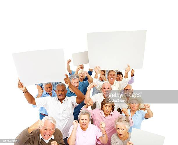 angry mob of old people with signs - mob stock photos and pictures