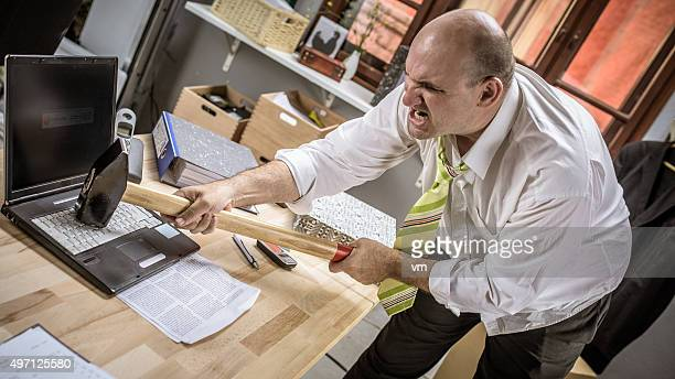 Angry office worker destroying his laptop with a sledgehammer