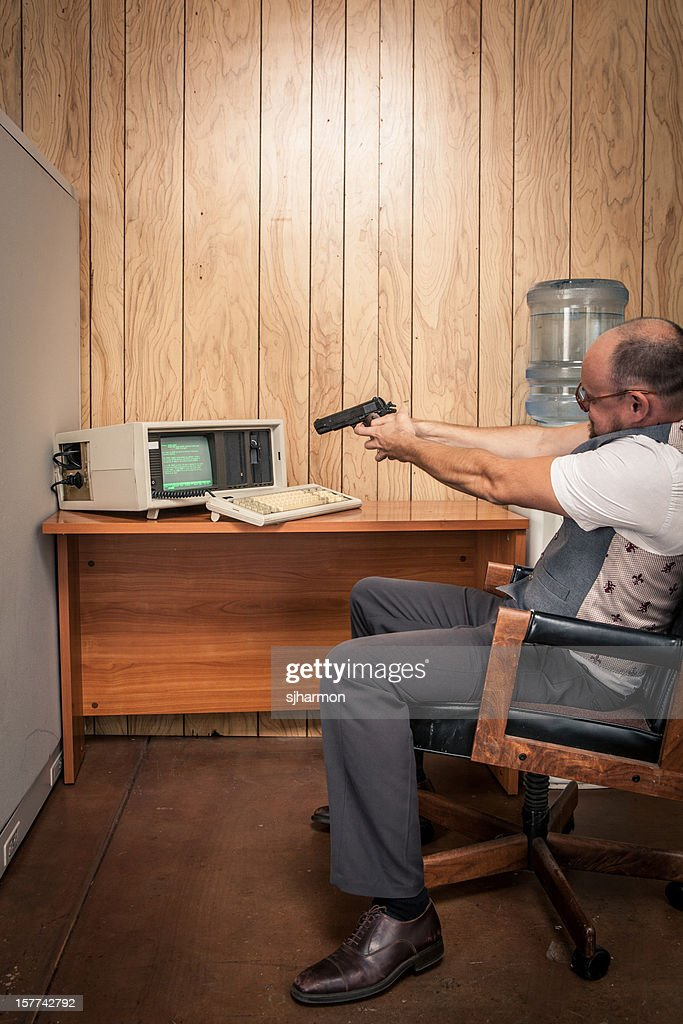 Angry office working aiming gun at old computer : Stock Photo