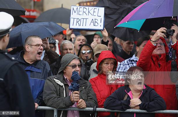 Angry onlookers including one holding a sign that reads Merkel resign shout Merkel muss weg and Volksverraeter outside the Semperoper opera house...