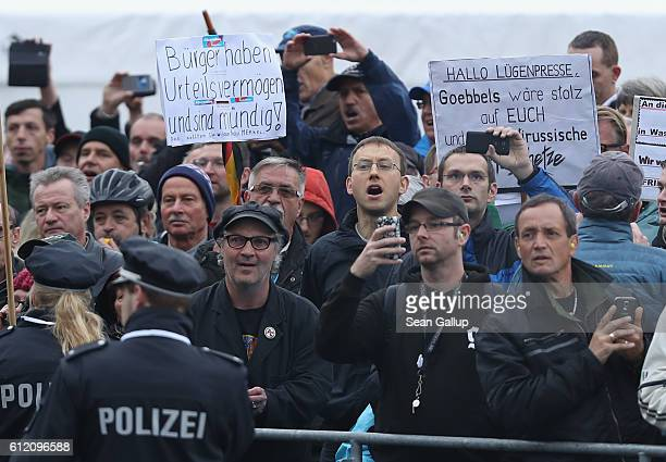 Angry onlookers shout Merkel muss weg and Volksverraeter outside the Frauenkirche church prior to celebrations to mark German Unity Day on October 3...