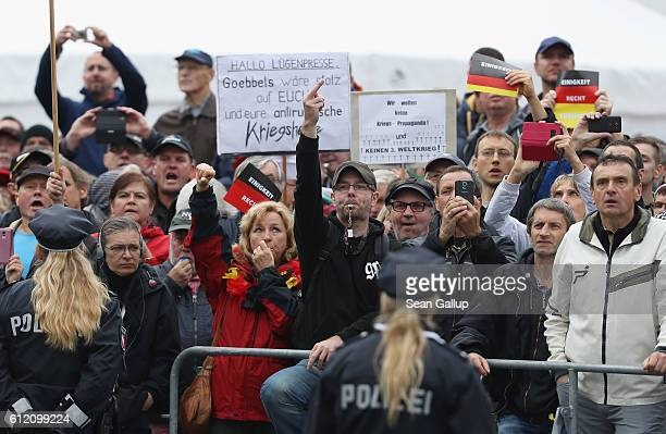 Angry onlookers shout Merkel muss weg and Volksverraeter outside the Frauenkirche church where German Chancellor Angela Merkel and other leading...