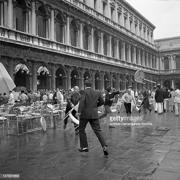 Angry people tossing tables and chairs during disorders due to the demonstration against the Biennale Venice 1968