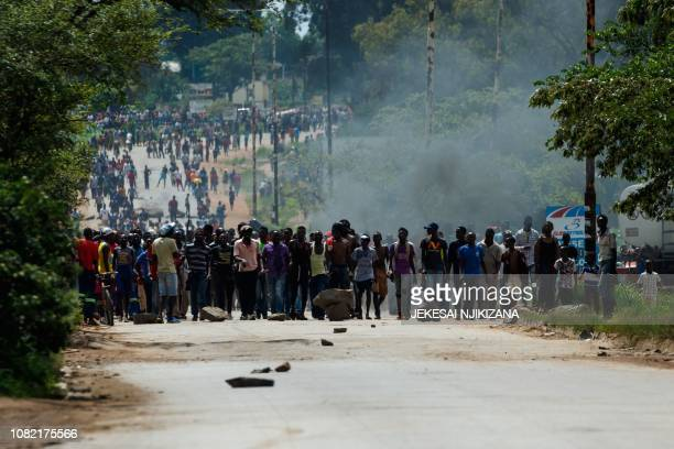 TOPSHOT Angry protesters barricade the main route to Zimbabwe's capital Harare from Epworth township on January 14 2019 after announced a more than...