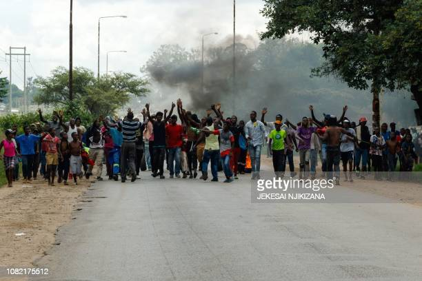 Angry protesters gesture as they block the main route to Zimbabwe's capital Harare from Epworth township on January 14 2019 after announced a more...