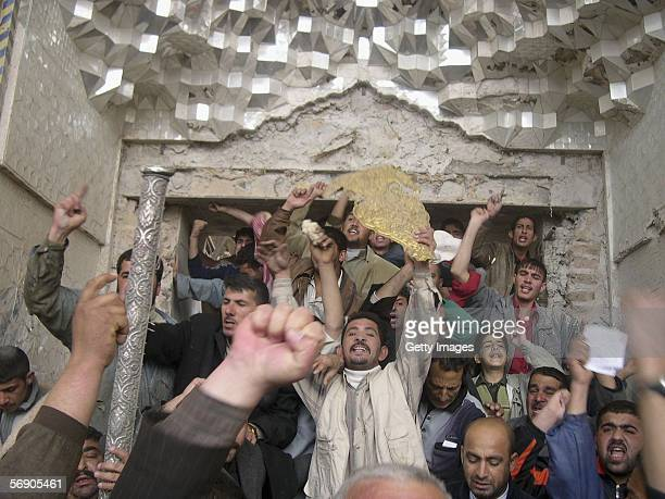Angry protesters shout slogans as one of them holds a golden piece of debris retrieved from inside the Shiite holy shrine of Ali alHadi on February...