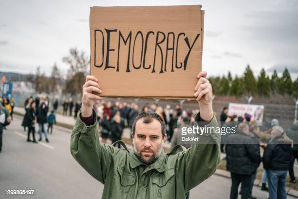 angry protestor holding a banner with text democracy on a street - placard stock pictures, royalty-free photos & images