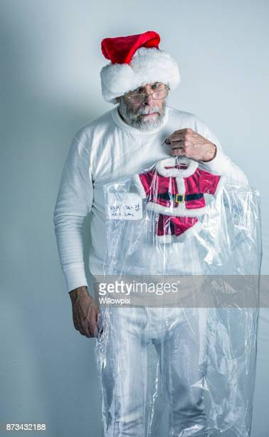 angry santa claus holding shrunken dry cleaned santa costume - santa face stock photos and pictures