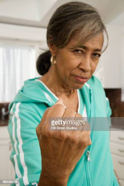 angry senior african woman making a fist - black pants fotografías e imágenes de stock